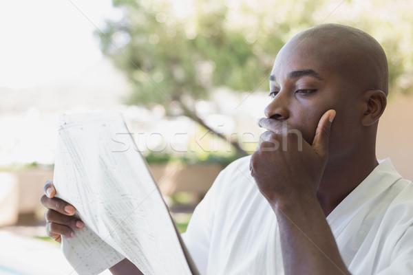 Knappe man badjas lezing krant buiten Stockfoto © wavebreak_media