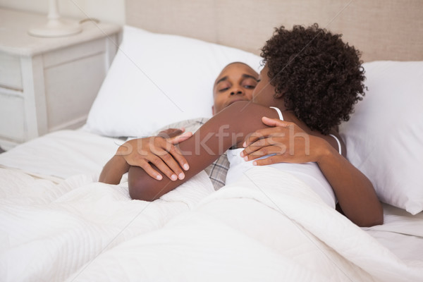 Happy couple in bed together Stock photo © wavebreak_media