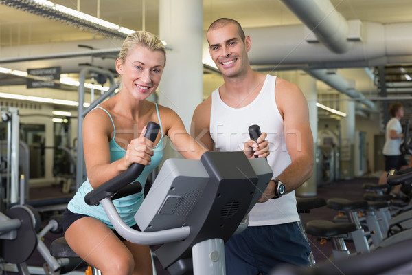 Male trainer assisting woman with exercise bike at gym Stock photo © wavebreak_media