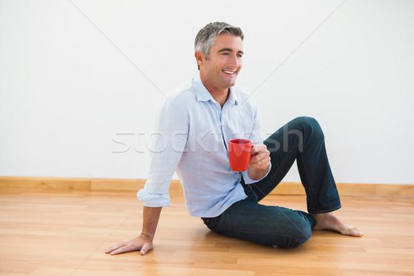 Sonriendo hombre sesión taza descalzo apartamento Foto stock © wavebreak_media