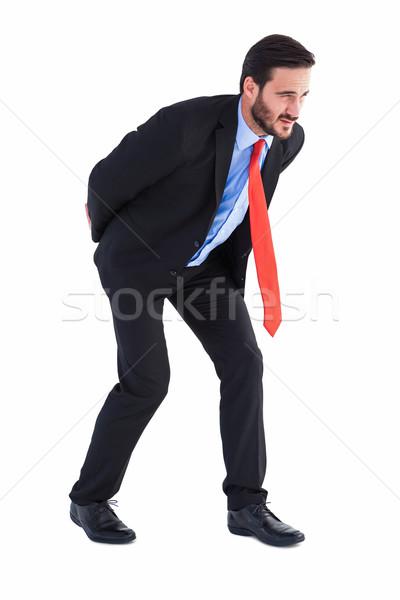 Businessman in suit carrying something heavy Stock photo © wavebreak_media