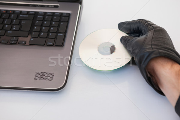 Burglar hacking and putting a cd-rom in laptop Stock photo © wavebreak_media