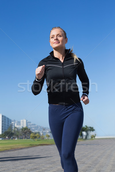 Stock photo: Fit blonde jogging on the pier