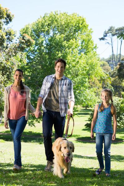 Happy family walking their dog in the park Stock photo © wavebreak_media