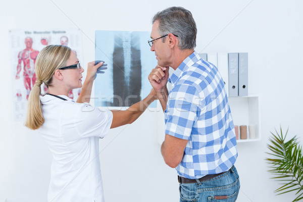 Doctor showing X rays to her patient  Stock photo © wavebreak_media