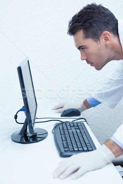 Zagęszczony mężczyzna dentysta patrząc monitor komputerowy widok z boku Zdjęcia stock © wavebreak_media