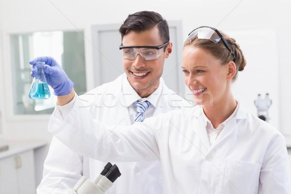 улыбаясь глядя химический стакан лаборатория женщину Сток-фото © wavebreak_media