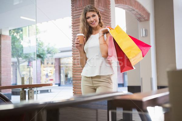 Portrait of smiling woman with shopping bags and coffee to go lo Stock photo © wavebreak_media