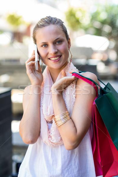 Mosolygó nő bevásárlótáskák hív mobiltelefon pláza vásárlás Stock fotó © wavebreak_media