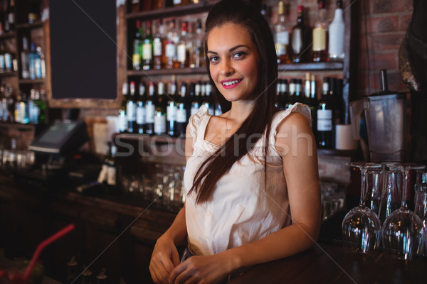 Female bartender standing at bar counter Stock photo © wavebreak_media