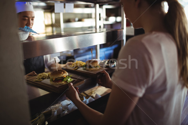 Chef passing tray with french fries and burger to waitress  Stock photo © wavebreak_media