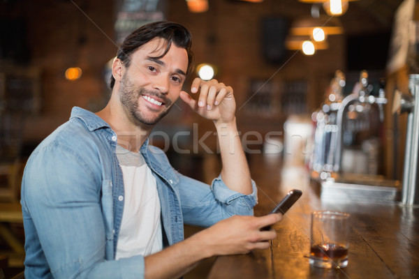 Young man using mobile while sitting at pub Stock photo © wavebreak_media