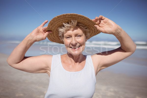 Stock photo: Portrait of senior woman wearing sun hat at beach