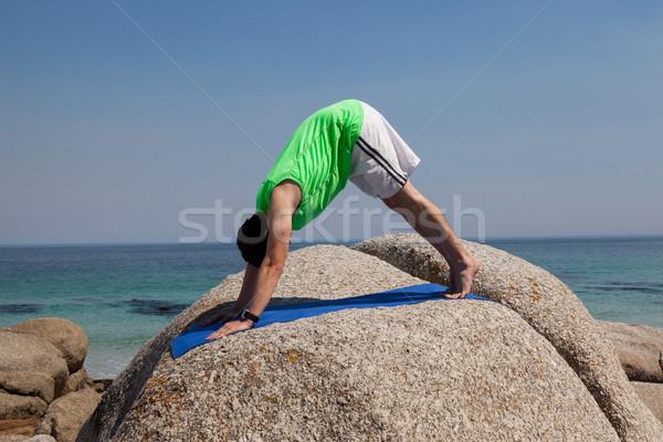 Man performing yoga on rock Stock photo © wavebreak_media