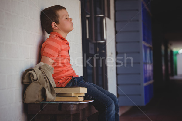 Sad boy with eyes closed sitting on bench by wall in corridor Stock photo © wavebreak_media