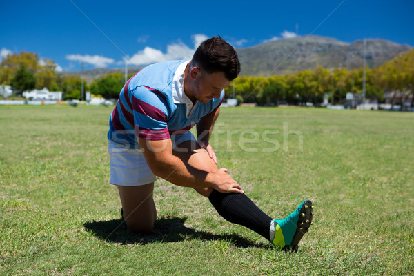 Young rugby player stretching on grassy field Stock photo © wavebreak_media