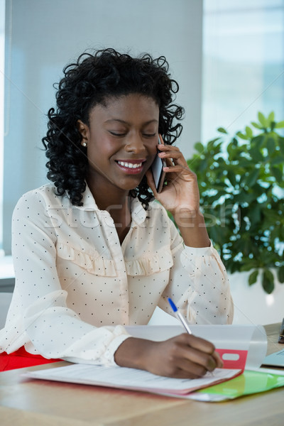 Female executive talking on mobile phone while working at desk Stock photo © wavebreak_media