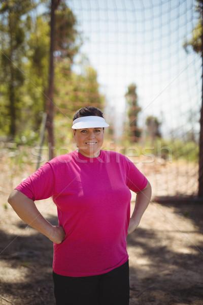 Portrait of happy woman standing with hands on hip in boot camp Stock photo © wavebreak_media