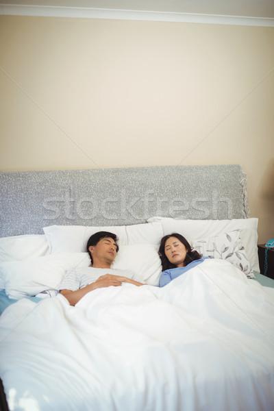 Couple sleeping on bed in bedroom Stock photo © wavebreak_media