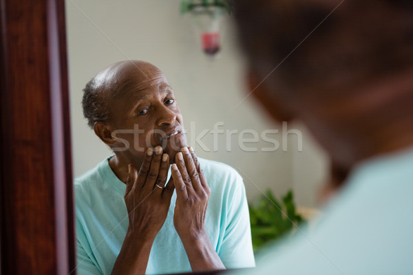 Concerned senior man looking at mirror Stock photo © wavebreak_media