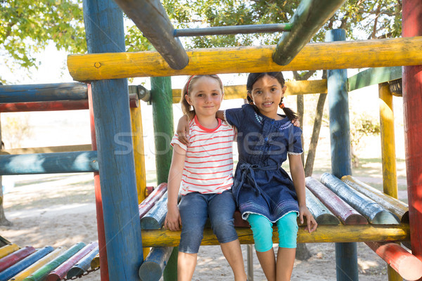 Portrait of smiling girls with arms around sitting on jungle gym Stock photo © wavebreak_media