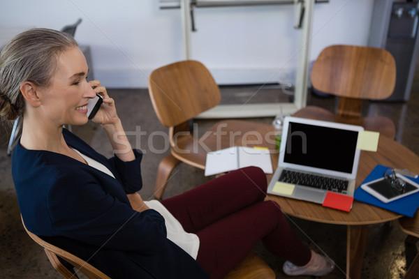 笑みを浮かべて 女性実業家 話し 電話 オフィス 座って ストックフォト © wavebreak_media