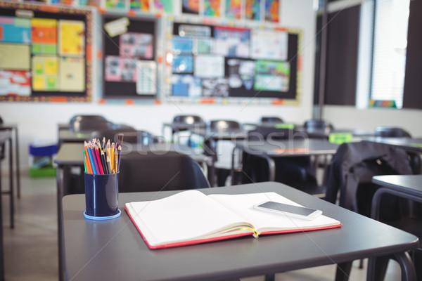 мобильного телефона открытой книгой столе классе книга школы Сток-фото © wavebreak_media