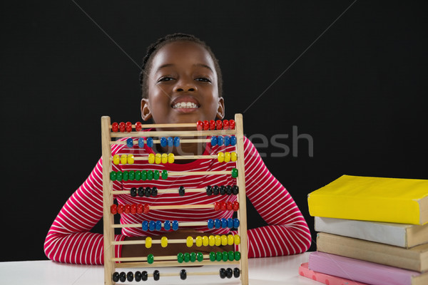Cute girl with abacus against black background Stock photo © wavebreak_media