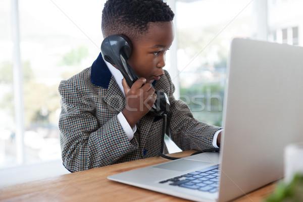 Businessman with laptop talking on telephone at desk Stock photo © wavebreak_media