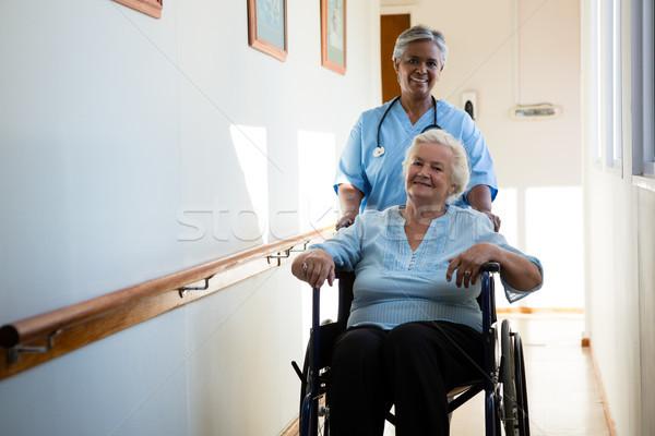 Enfermeira empurrando paciente sessão cadeira de rodas casa de repouso Foto stock © wavebreak_media