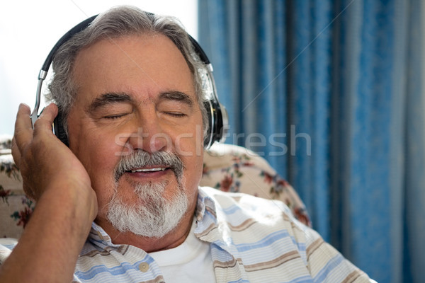 Senior man listening music through headphones in nursing home Stock photo © wavebreak_media