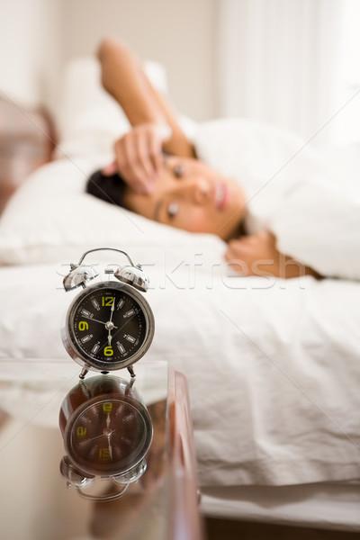 Alarm clock against brunette on bed Stock photo © wavebreak_media