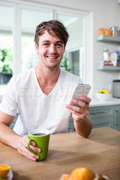 Homem bonito copo cozinha telefone Foto stock © wavebreak_media