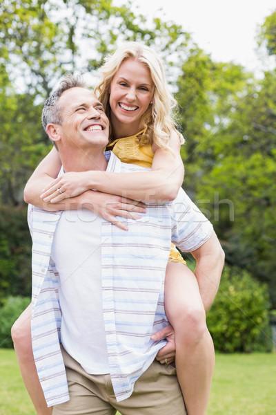 Happy husband giving piggy back to his wife Stock photo © wavebreak_media