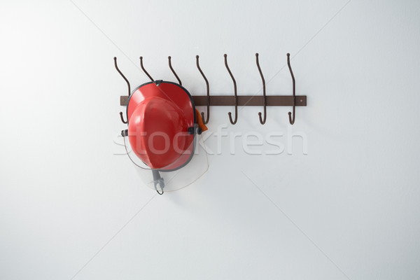 Piros munkavédelmi sisak akasztás kampó fehér fal Stock fotó © wavebreak_media