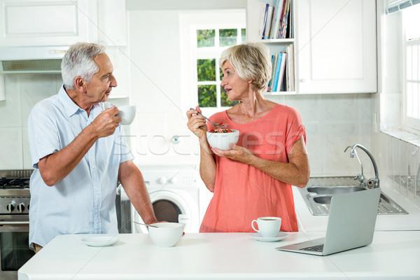 Foto stock: Feliz · casal · de · idosos · café · da · manhã · em · pé · cozinha · computador