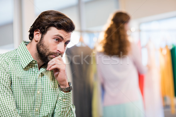 Bored man waiting his wife while woman by clothes rack Stock photo © wavebreak_media