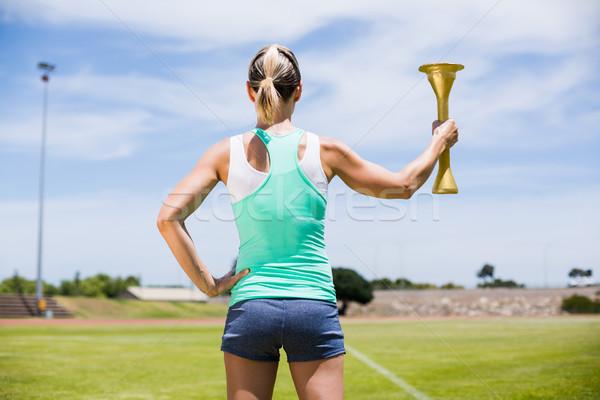 Rückansicht weiblichen Athleten halten Feuer Taschenlampe Stock foto © wavebreak_media