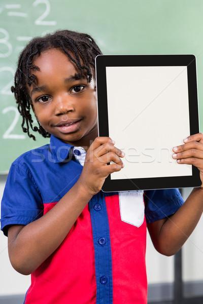 Smiling boy holding digital tablet in classroom Stock photo © wavebreak_media