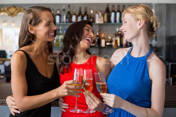 Happy female friends holding glass of champagne flute Stock photo © wavebreak_media