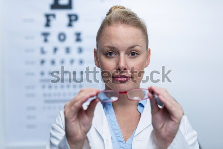 Smiling female optometrist holding spectacles Stock photo © wavebreak_media