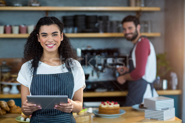 Smiling waitress using digital tablet at counter in café Stock photo © wavebreak_media