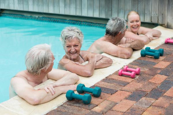 Cheerful swimmers leaning on poolside Stock photo © wavebreak_media