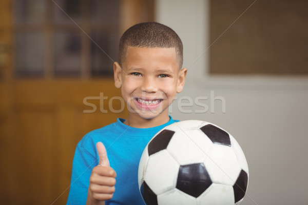 Smiling pupil holding football and doing thumbs up Stock photo © wavebreak_media