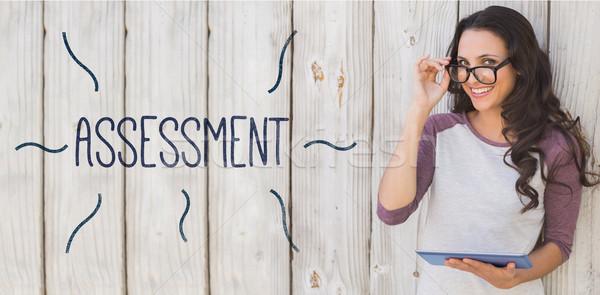 Assessment against pretty brunette using a tablet pc Stock photo © wavebreak_media