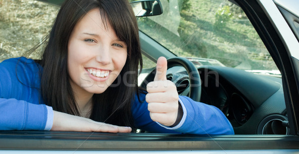 Happy teen girl with a thumb up sitting in her car  Stock photo © wavebreak_media