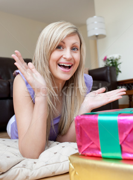 Astonished pretty woman opening gifts lying on the floor Stock photo © wavebreak_media