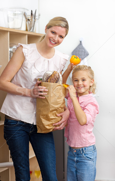 Happy mother and her Little girl unpacking grocery bag in the kitchen Stock photo © wavebreak_media
