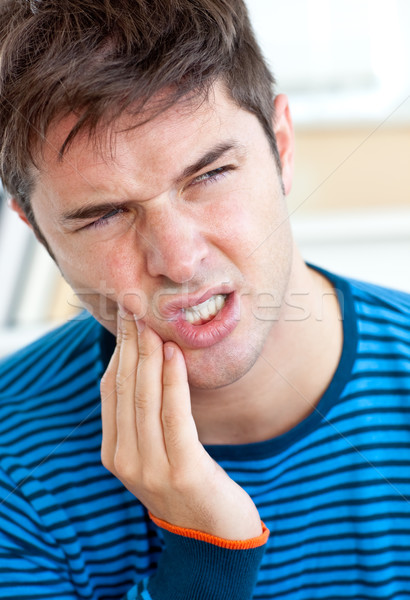 Unhappy caucasian man having a toothache in the living-room at home Stock photo © wavebreak_media