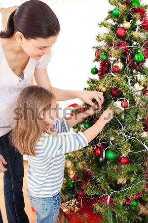 Attentive father holding her daughter to decorate the christmas tree in the living room Stock photo © wavebreak_media